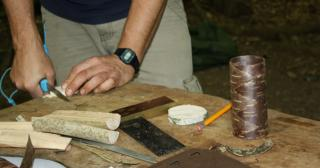 Carving a wooden lid for a birch bark container