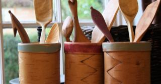 Hand carved wooden spoons and spatulas in birch bark tubs